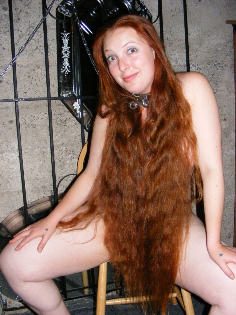 Nude girl covered by her long red hair.