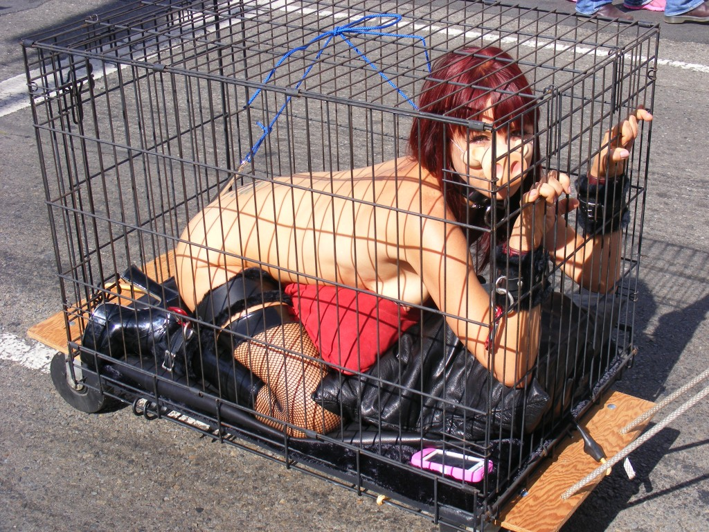 Nude slave girl in cage on public street at Folsom Street Fair