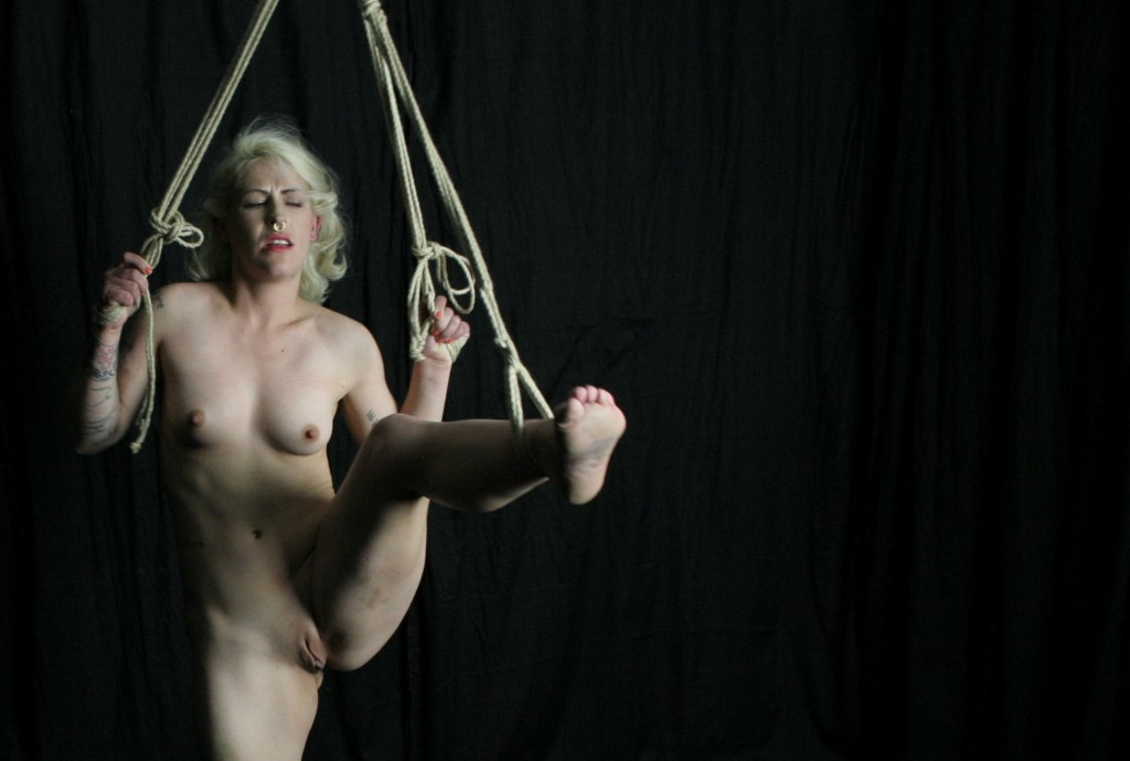 Naked slave girl tied with legs spread wide showing her shaved pussy