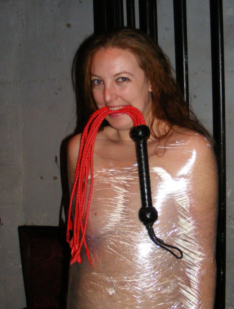 Nude Slave Girl bound in Saran Wrap with flogger in mouth and big grin