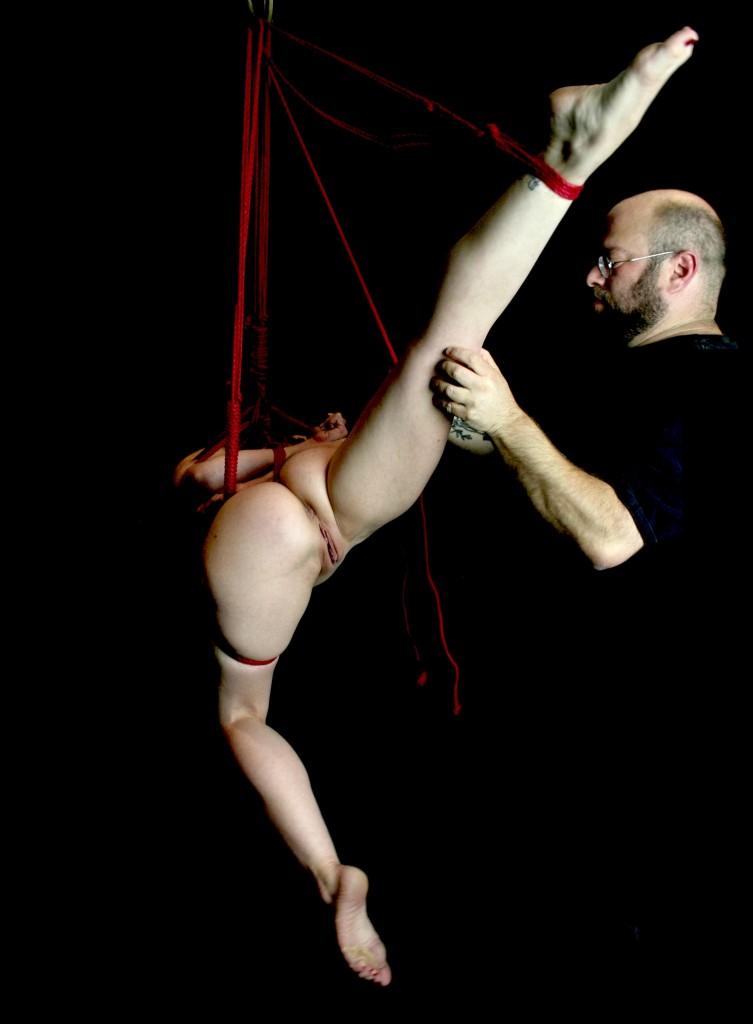 Nude slave girl with spread legs in suspension bondage