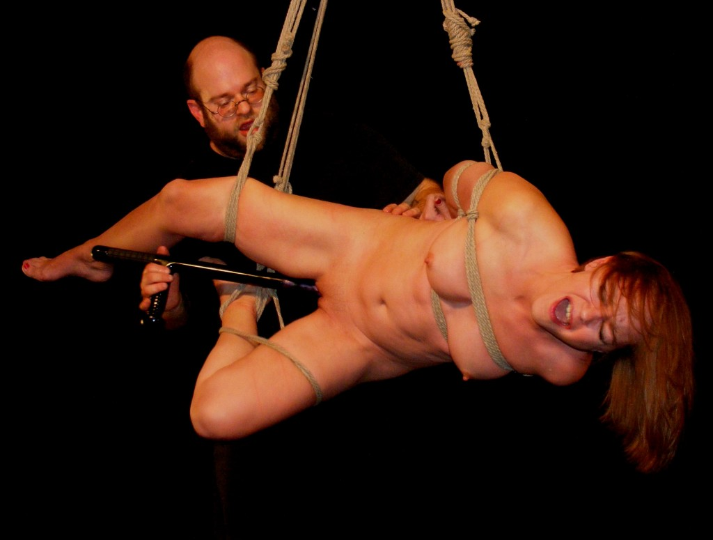Nude slave girl in shibari bondage being fucked with night stick