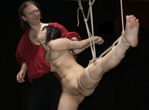 Nude slave girl in hsibari bondage with legs spread and shaved pussy attempts to kiss her master