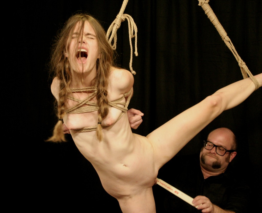 Nude slave girl in shibari bondage having her shaved pussy spanked