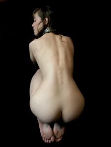 Naked collared Gorean slave girl on her knees.