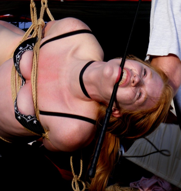 Madison Young in suspension bondage in public gagged with a riding crop