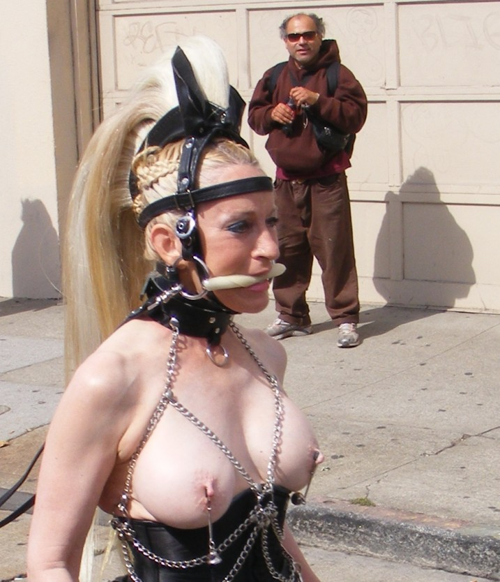 Pony girl with bit gag and bells on her nipple clips in public