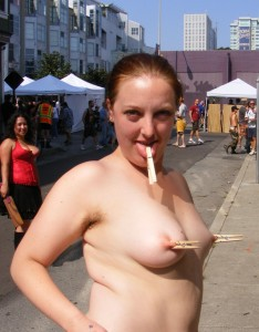 Nude girl on public street with clohes pegs on her nipples and tongue.