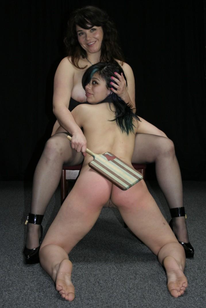 Lesbin mistress paddling her nude slave girl's ass.