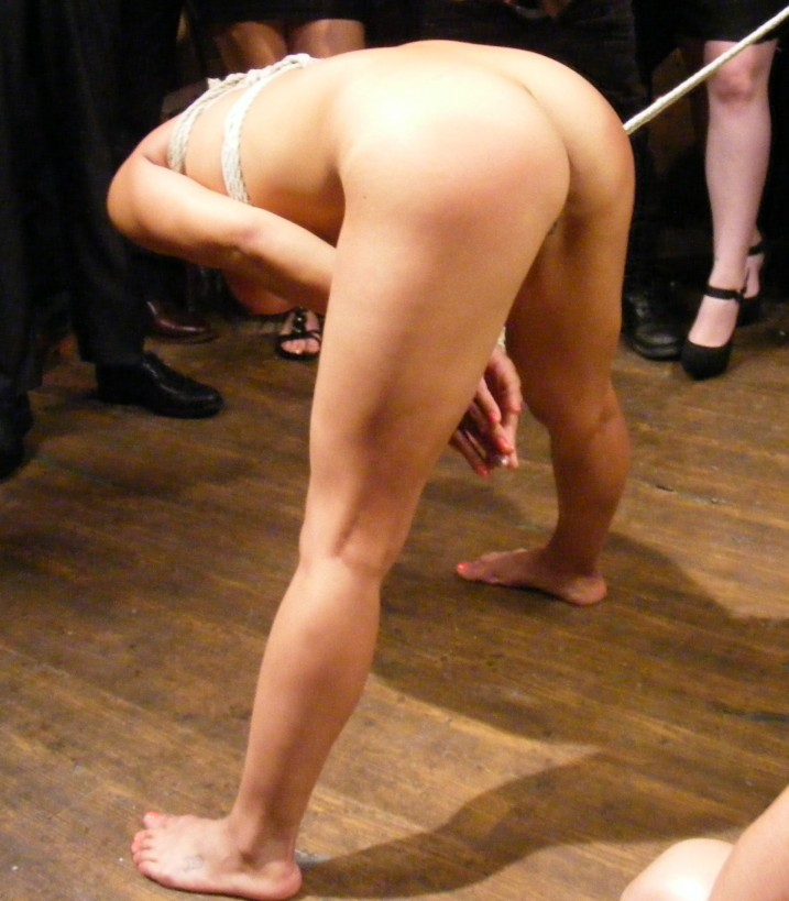 Nude slave girl bending over to be caned