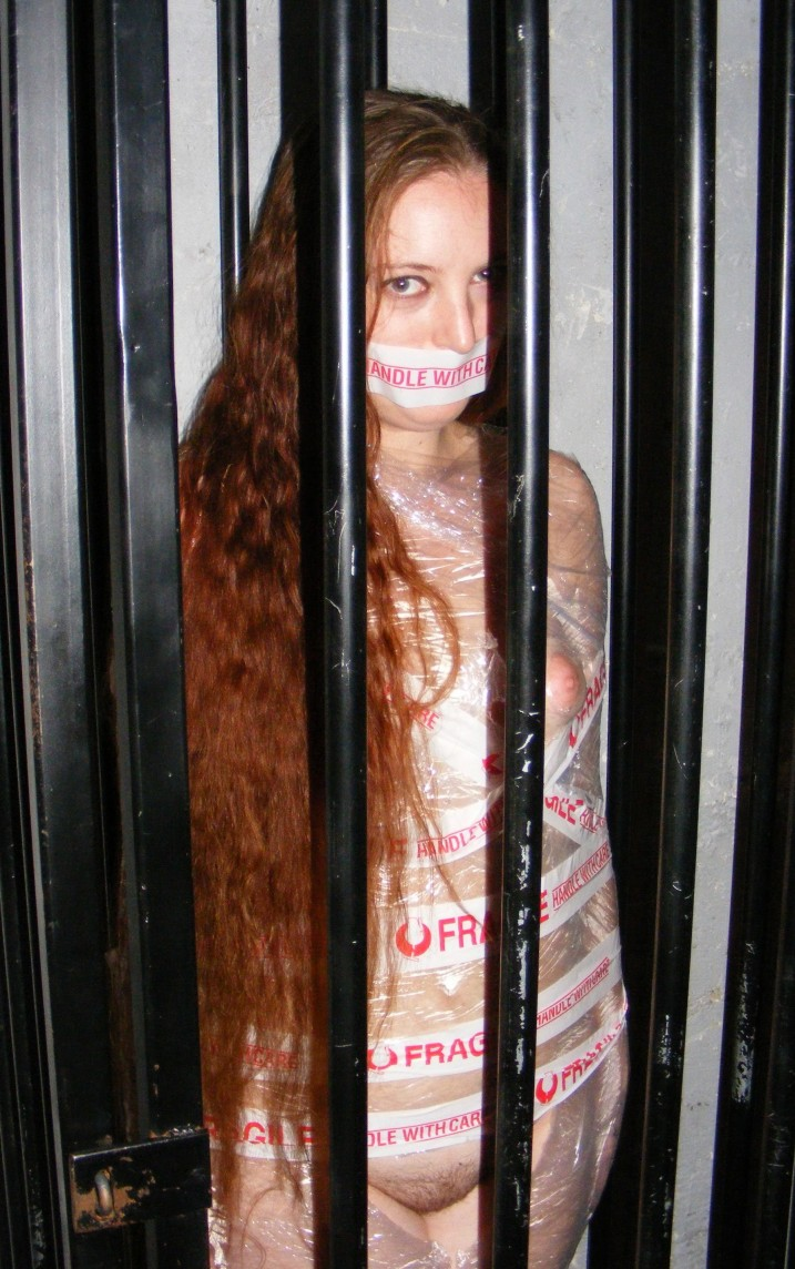 Lacey Field, bound and gagged redhead, nude in prison cell.