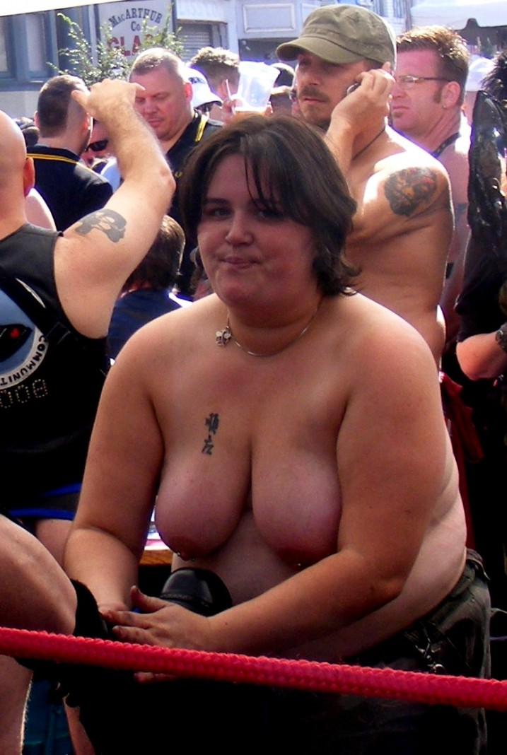 Topless girl polishing boots in public