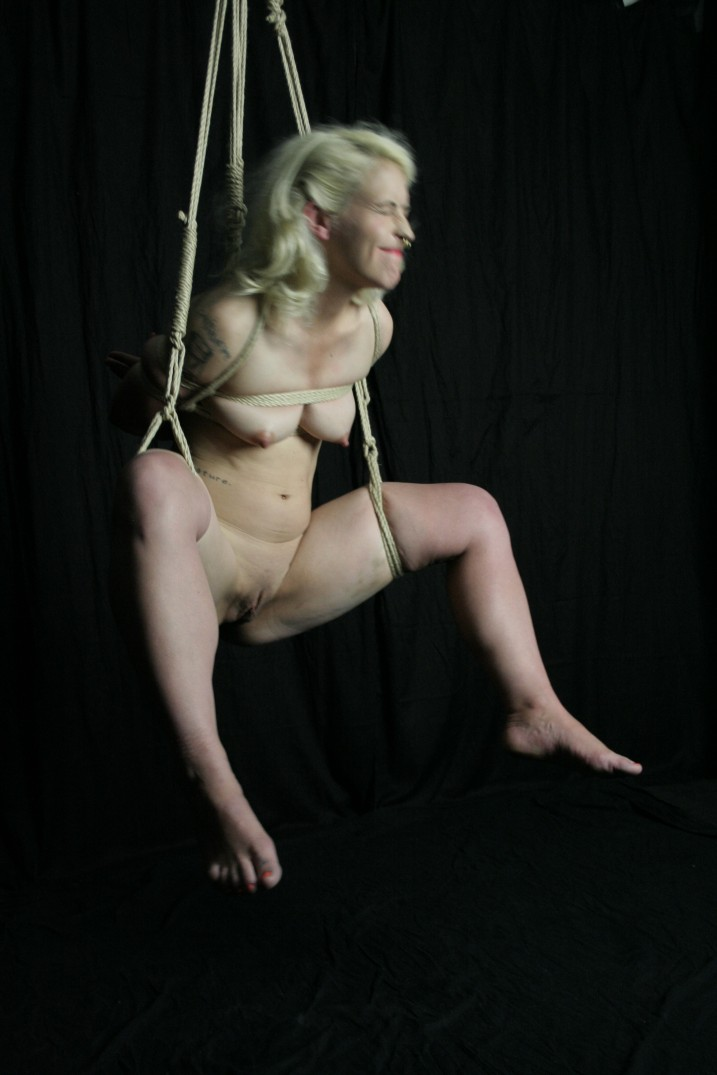 Slave girl in shibari suspension bondage with legs spread wide showing shaved pussy