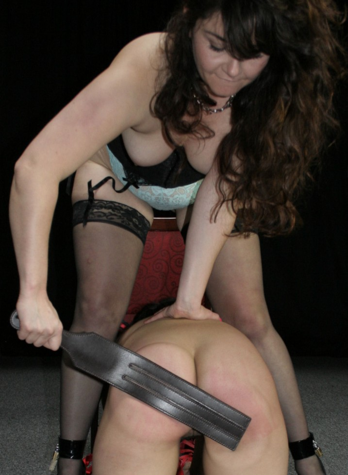 Mistress spanking her nude slave girl with a tawse.