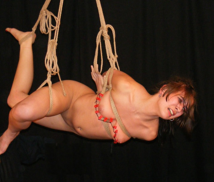 Nude slave girl in suspension bondage with tits being tortured by nipple clips in zipper.