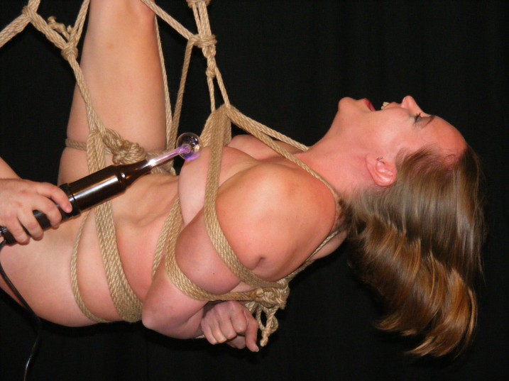Nude slave girl in suspension bondage having nipples tortured with violet wand.