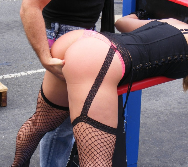 Slave girl in stocks at Folsom Street Fair having her bare ass and pussy fingered