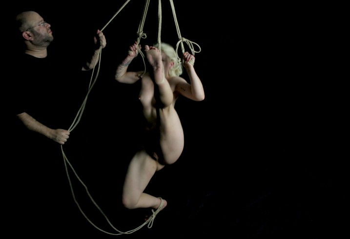 Naked slave in shibari bondage tied with legs spread