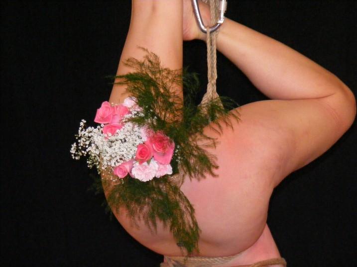 Naked slave girl suspended upside down with a bunch of flowers stuck in her ass