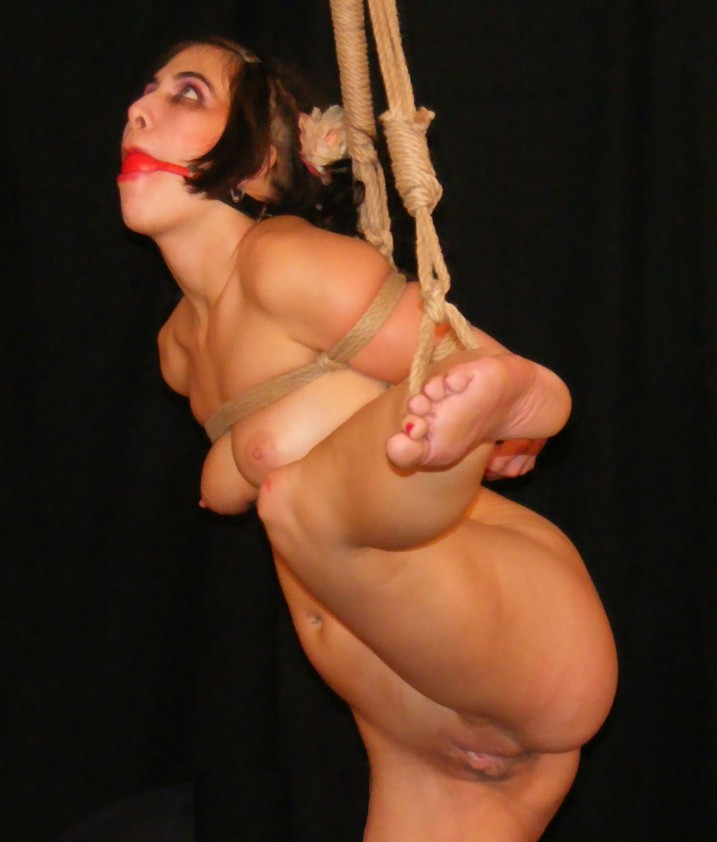 Naked slave girl with ball gag tied with legs spread showing shaved pussy