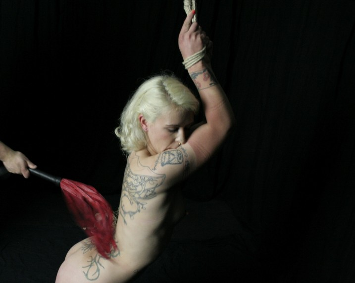 Tattooed naked slave girl bound and whipped